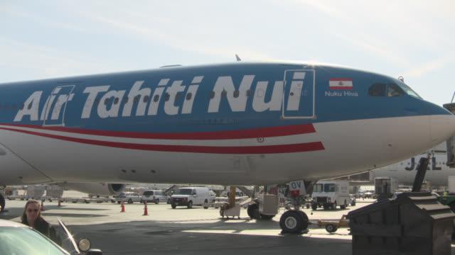 vídeos y material grabado en eventos de stock de zoom in on air tahiti nui airplane at airport terminal. - escritura occidental