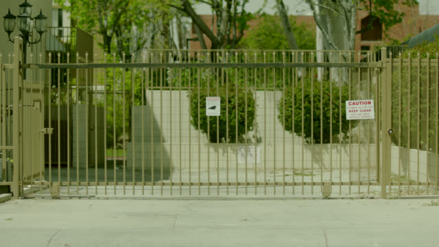 CLOSE ANGLE OF GATED DRIVEWAY. COULD BE APARTMENT BUILDING.