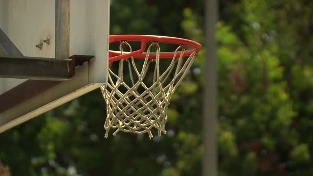 CLOSE ANGLE OF BASKETBALL GOING THROUGH BASKETBALL HOOP.