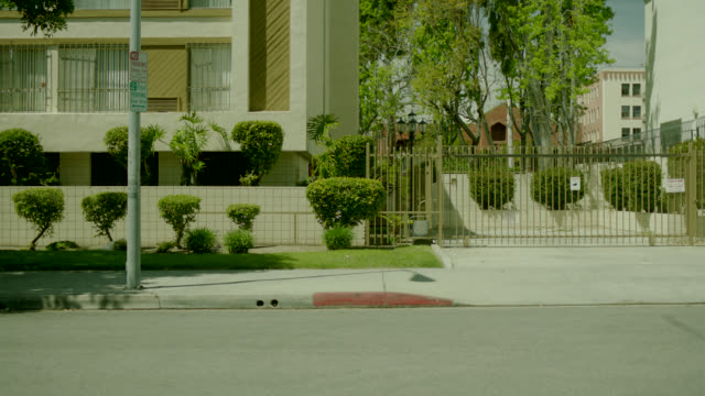 vídeos de stock, filmes e b-roll de medium angle rack focus of gated driveway. gates opens and closes. could be apartment building. - portão