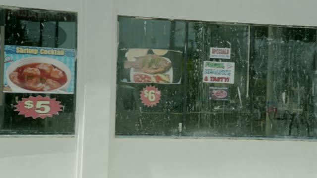 MEDIUM ANGLE OF FOOD ADVERTISEMENTS ON RESTAURANT WINDOW.