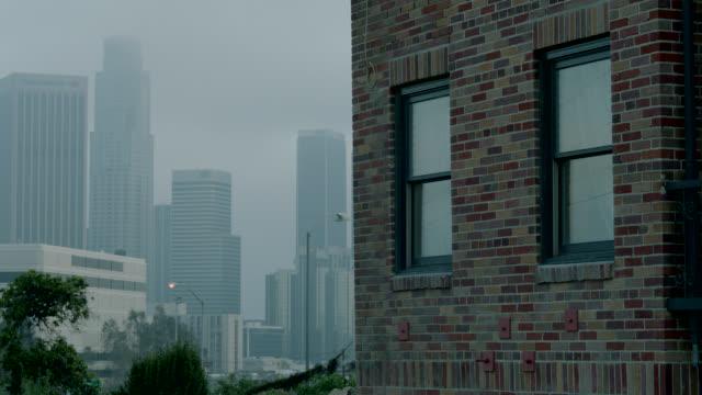 MEDIUM ANGLE OF APARTMENT BUILDING WINDOW. BRICK BUILDING. CITY SKYLINE IN BG.