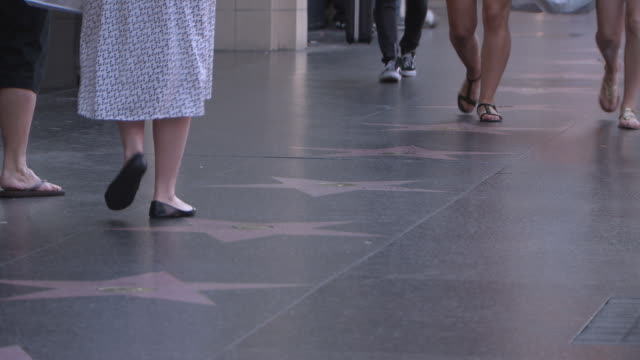 medium angle of people, pedestrians walking on hollywood walk of fame. landmarks. - walk of fame stock videos and b-roll footage