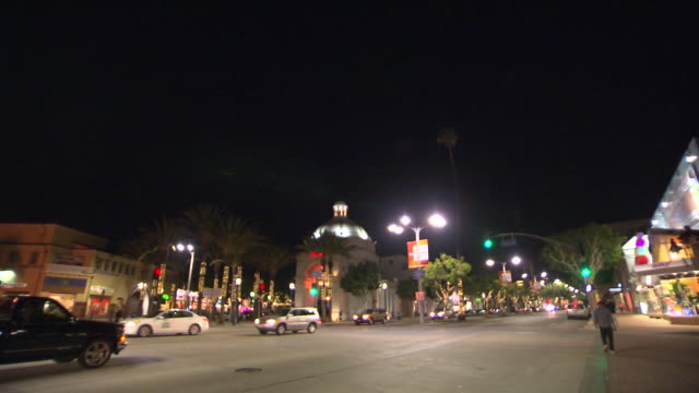 PAN DOWN TO CARS ON CITY STREETS. WESTWOOD VILLAGE.