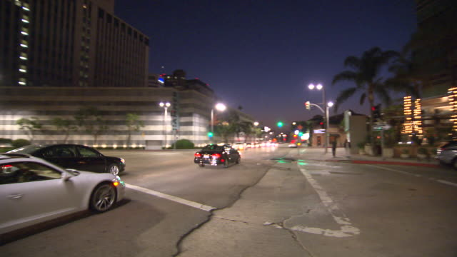 pan left to right of cars in city street intersection. hammer museum in bg. westwood village. - westwood neighborhood los angeles stock videos & royalty-free footage