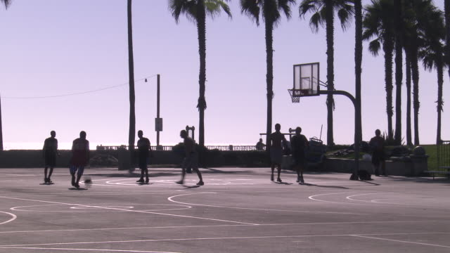 wide angle of people playing basketball on court near ocean. - コート点の映像素材/bロール