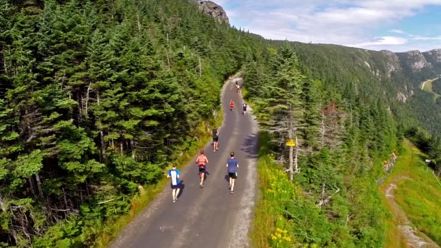 hundreds of runners start up mountain road in race aerial - salmini stock videos & royalty-free footage