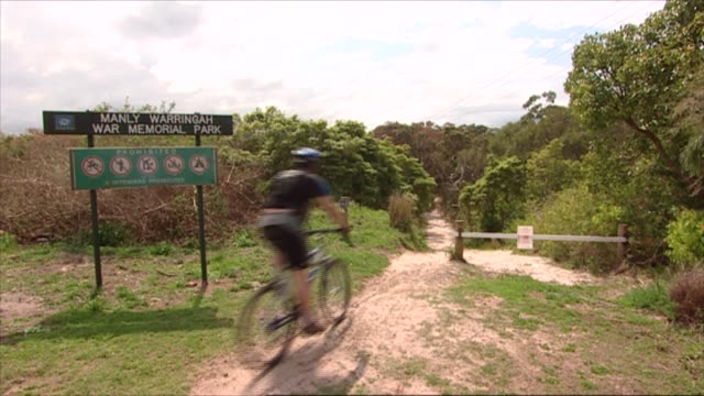 north balgowlah - grassed area with track leading to bush/ vs scrub with burnt bush on one side / mcu sign 'manly warringah war memorial park' /... - war stock-videos und b-roll-filmmaterial
