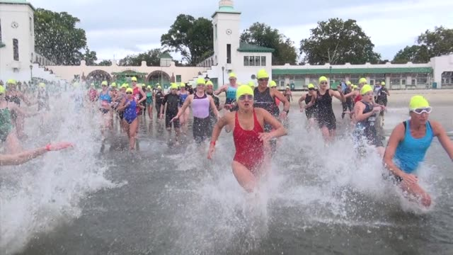 KIDS AND ADULTS CHARGE INTO WATER TO START A TRIATHLON