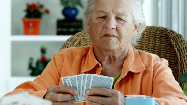 vídeos de stock e filmes b-roll de elderly woman playing cards - carta de baralho