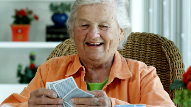 elderly woman playing cards - carte da gioco video stock e b–roll