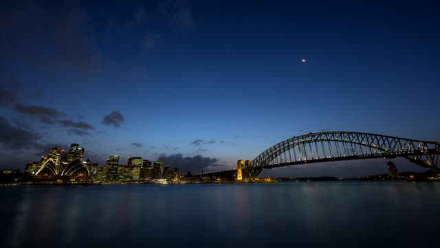 low angle timelapse dusk to night looking south west sydney opera house and circular quay framed by city skyline with sydney harbour bridge on right... - bennelong point stock videos and b-roll footage