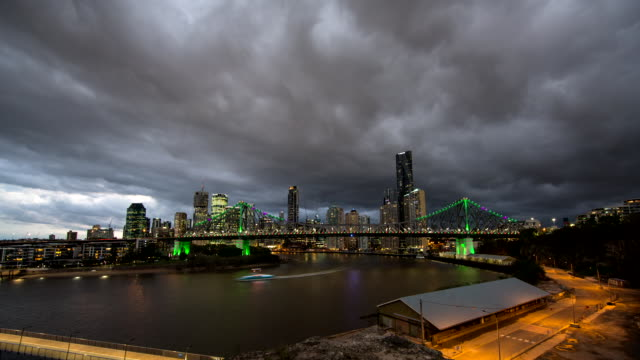 dusk timelapse dark storm clouds over wide shot story bridge with brisbane city behind building lights brighten lights frame bridge span and supports... - stimmungsvoller himmel stock-videos und b-roll-filmmaterial