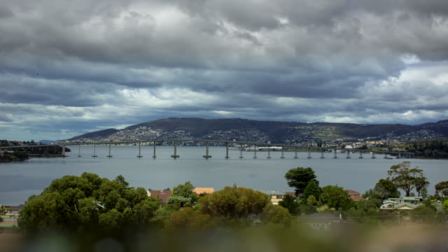 timelapse pov from lindsifarne thick half gray clouds roll above wide shot tasman bridge over derwent river hobart minimal water craft traffic on... - ridge stock videos & royalty-free footage