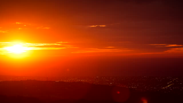 DUSK TO NIGHT SUNSET TIMELAPSE WIDE HIGH SHOT POV FROM ADELAIDE HILLS LOOKING WEST ADELAIDE HILLS BUSHLAND IN FOREGROUND SUBURBAN STRIP WITH LIGHTS...