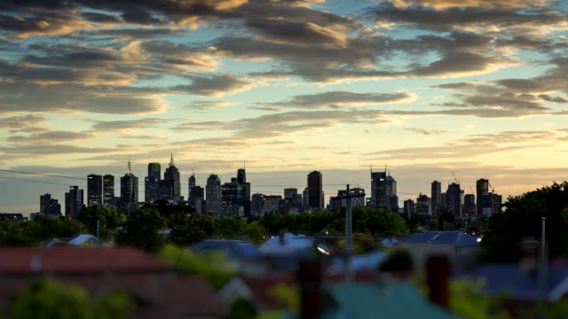 timelapse dusk to night low angle over suburban rooftops clouds moving across melbourne city sky line city turns to dark as building lights illuminate - zeitraffer tag bis nacht stock-videos und b-roll-filmmaterial