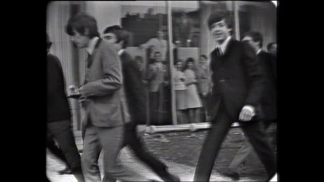 the beatles leave hotel rooftop balcony surrounded by entourage and press paul mccartney waves to camera pan to crowd at street level / beatles we... - hysteria stock videos & royalty-free footage