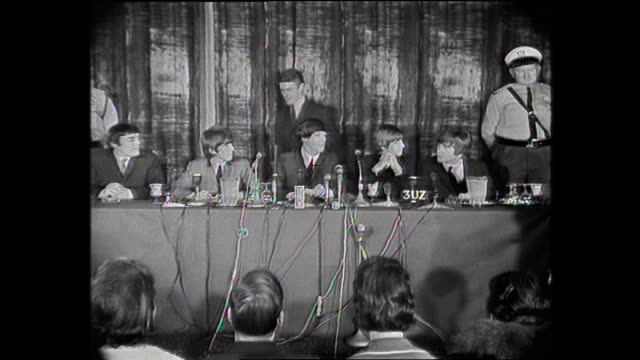 various shots the beatles waiting at melbourne press conference as security officers stand behind– all of them smoking ringo puts three cigarettes in... - ringo starr bildbanksvideor och videomaterial från bakom kulisserna