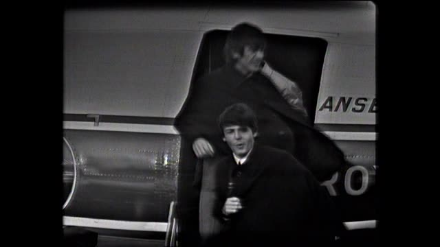 steps pushed up to ansett-ana plane on tarmac and plane door opened / fans wait / air hostesses alight / the beatles emerge as girls scream - paul... - paul mccartney stock videos & royalty-free footage