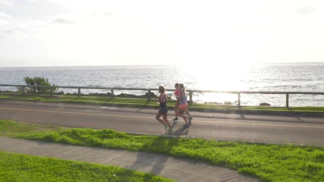 runners along ocean, sunrise - salmini stock videos & royalty-free footage
