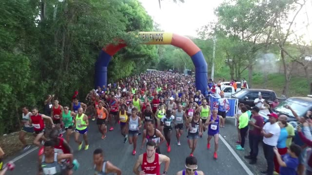 vidéos et rushes de drone, running race start, drone moves out with runners - salmini