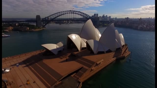 drone aerial sydney harbour bridge seen over tip of opera house sail zoom out over opera house and back as harbour cruise boat passes behind... - bennelong point stock videos and b-roll footage