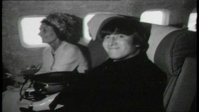 the beatles on plane en route to australia close up paul macartney reads book on plane / john lennon sitting with aunt stares turns towards camera... - john lennon stock videos and b-roll footage