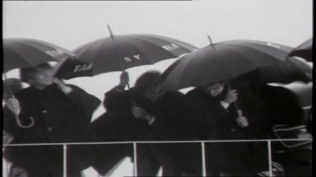 THE BEATLES ARRIVE IN SYDNEY FROM LONDON BOAC PLANE TAXIS ON TARMAC UPSOT SCREAMING FANS / POLICE HOLD BACK FANS AT BARRICADE / THE BEATLES OFF PLANE...