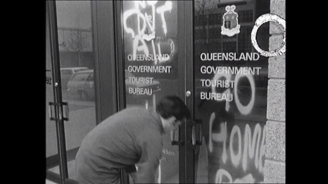 antispringboks slogans have been painted on the doors of the queensland tourist bureau protesting the qld government granting leave for the south... - hakenkreuz stock-videos und b-roll-filmmaterial