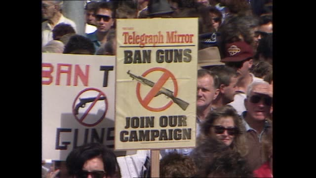 leigh hatcher reports: wide shot pro gun control laws rally in park / iv sue pascoe / protest organiser with loud speaker / protestor holds sign... - gun stock videos & royalty-free footage