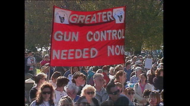 various shots anti gun rally people stand exterior parliament house hobart / banner greater gun control needed now / people stand at rally / kid with... - protesta contro la violenza armata video stock e b–roll