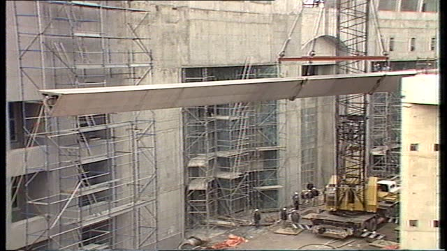various shots of workers preparing for flagpole leg to be lifted/ alternate shots of flagpole leg being lifted in crane with workers assisting... - regierungsgebäude stock-videos und b-roll-filmmaterial