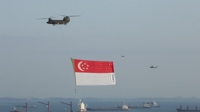 w/s panning shot of helicoptor carrying giant singapore flag,cargo ships in b/g ,national day - helicopter stock videos and b-roll footage
