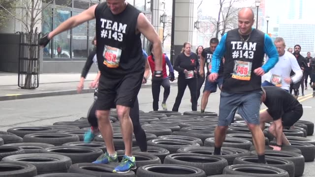 obstacle racers work their way through tire maze before continuing on the course - salmini stock videos & royalty-free footage