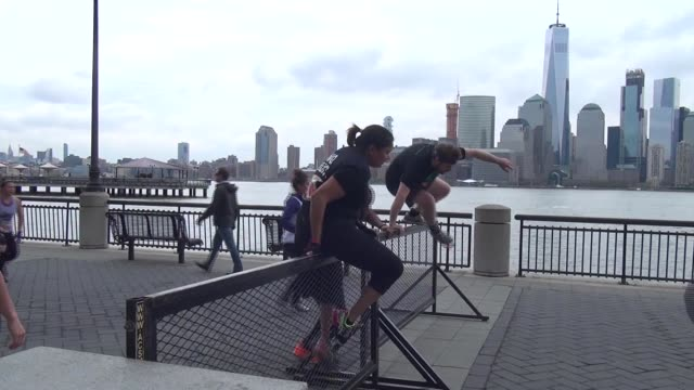 obstacle racers must get over hurdle to continue. freedom tower, one world trade center across hudson river in background. - salmini stock videos & royalty-free footage