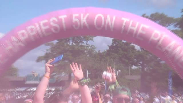 runners covered with pink as they move through the course - flushing meadows corona park stock videos and b-roll footage