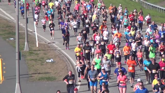 zoom out to reveal thousands of runners in the long island marathon - salmini video stock e b–roll
