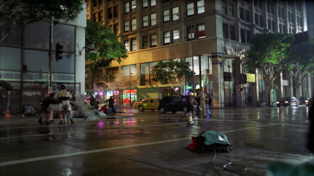 WIDE ANGLE OF 1973 OLDSMOBILE CAR DRIVING ON SIDEWALK AND CRASHING THROUGH TABLE AND FIRE HYDRANT. PEOPLE OR PEDESTRIANS RUNNING OUT OF THE WAY. POLICE CARS WITH FLASHING LIGHTS AND SIRENS. ACTUALLY DOWNTOWN LOS ANGELES. CAR STUNT. CAR CHASE.