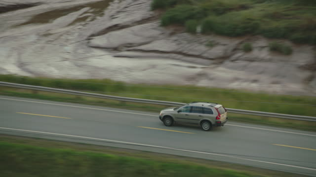vidéos et rushes de aerial tracking shot of car driving over bridge. river. highway through forests or woods. rural areas. - ligne à haute tension
