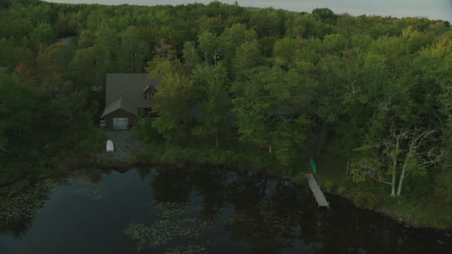 vídeos y material grabado en eventos de stock de aerial of lake and cabin, lake house, or vacation house. trees in forest or woods. - cabaña de madera