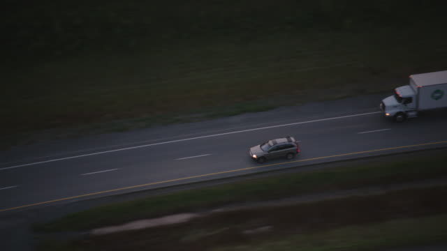 AERIAL OF CARS DRIVING ON HIGHWAY IN RURAL AREAS.