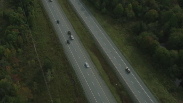 vidéos et rushes de aerial of car driving on road or highway through countryside or rural area. trees in woods or forest. - route de campagne