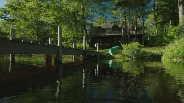pan left to right from docks on lake to two story cabin, lake or vacation house in bg. canoe on shore. trees. - log cabin stock videos & royalty-free footage