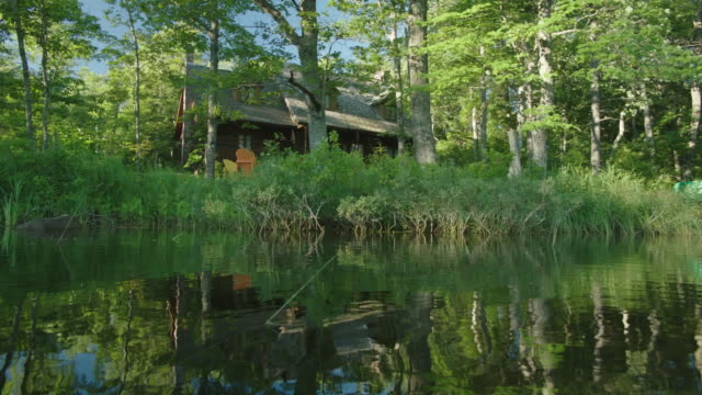 pan left to right of two story wooden cabin, lake or vacation house on shore of lake. trees in forest or woods. - outdoor chair stock videos and b-roll footage