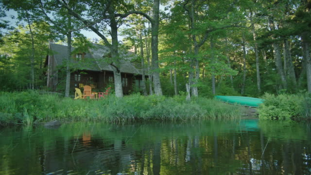 wide angle of two story cabin, lake or vacation house in bg. canoe on shore. trees. - wide stock videos & royalty-free footage