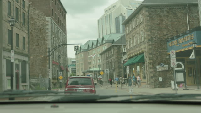 MEDIUM ANGLE DRIVING POV STRAIGHT FORWARD FROM DASHBOARD OF CITY STREETS IN DOWNTOWN HALIFAX, CANADA. MULTI-STORY OFFICE OR APARTMENT BUILDINGS. GPS DEVICE.