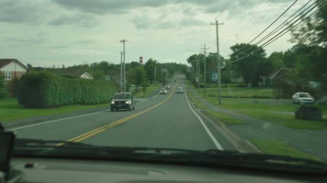 MEDIUM ANGLE DRIVING POV FROM DASHBOARD OF CAR. GPS DEVICE. SMALL TOWN, RURAL AREA OR COUNTRYSIDE. MIDDLE CLASS HOUSES.