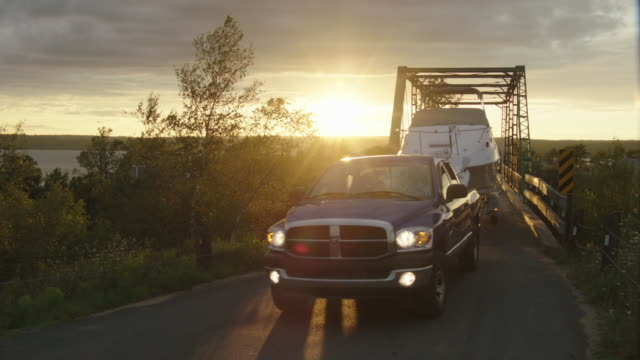 medium angle of pickup truck towing boat driving across truss bridge, followed by suv or car. - rimorchiare video stock e b–roll