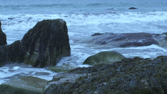 medium angle of waves hitting rocks on shore. could be beach. could be lake or ocean. - coastal feature stock videos & royalty-free footage