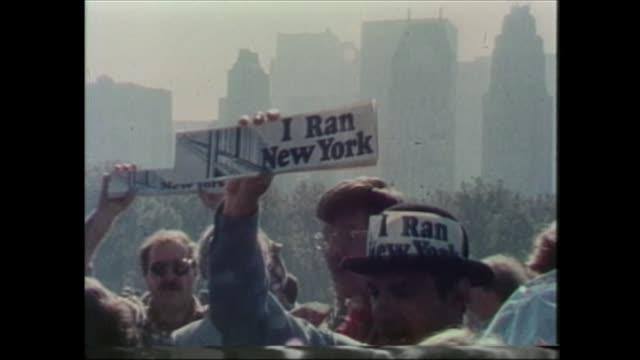 vidéos et rushes de i ran new york bumper sticker then runner makes phone call wearing space blanket. - marathon